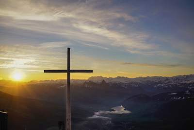 cross overlooking a river at dawn
